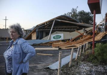 """A woman stands in front of a destroyed restaurant after Hurricane Zeta on Oct. 29, 2020, in Chalmette, La. In a postseason analysis, NOAA upgraded Zeta's windspeeds, saying it was a """"major"""" Category 3 storm when it hit."""