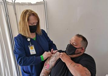 John Harrower, a truck driver from the Canadian province of Manitoba, receives a COVID-19 vaccine shot in North Dakota in late April.