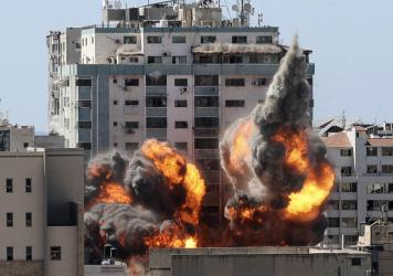 A ball of fire erupts from a building housing various international media, including The Associated Press, after an Israeli airstrike on Saturday in Gaza City. AP staffers and other tenants safely evacuated the building after the Israeli military telepho