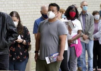 Voters are seen wearing masks in April as they prepared to cast ballots in Mansfield, Texas. The governor has now banned most state facilities from requiring masks.