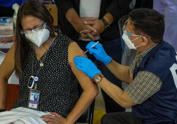 Philippines Health Secretary Francisco Duque III (right) administers the China-made Sinovac COVID-19 vaccine to Eileen Aniceto, a doctor at the Lung Center of the Philippines.