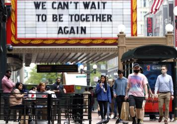 People walk near the Chicago Theatre on Tuesday in the city's Loop community. The Centers for Disease Control and Prevention eased its guidelines on the wearing of masks, saying fully vaccinated Americans don't need to cover their faces anymore in most s