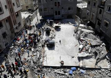 People gather near the rubble of a residential building hit by Israeli airstrikes Thursday in Beit Lahiya, Gaza Strip.