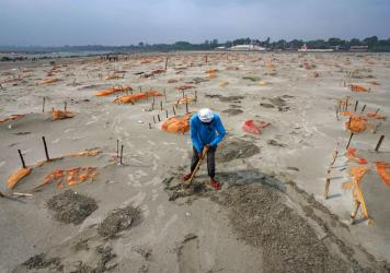 Rains have washed away the top layer of sand of shallow graves at a cremation ground on the banks of the Ganges River in Shringverpur, northwest of Allahabad, Uttar Pradesh, India. Coronavirus testing is limited in parts of rural India, but some of the p