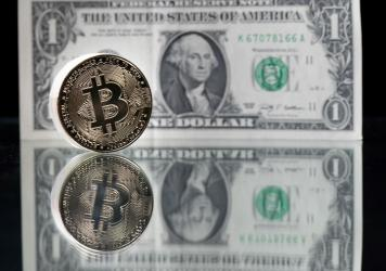 A physical imitation of the Bitcoin cryptocurrency is pictured with a $1 bank note. Cryptocurrencies are plunging over a range of factors, including the spillover impact from falling stock markets and fears about increased regulations.
