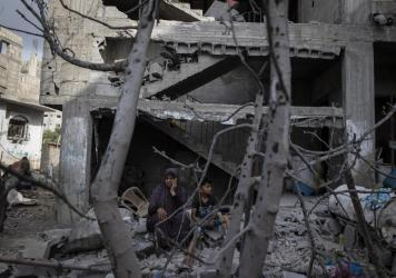 A Palestinian woman sits with her son in front of her destroyed house in the town of Beit Hanoun, northern Gaza Strip, to which she returned following a cease-fire reached after an 11-day war between Gaza's Hamas rulers and Israel.