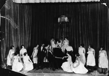 American composers and musicians Noble Sissle, center left, and Eubie Blake, on piano, perform with a group of women on stage in the early 20th century. Sissle and Blake wrote the score for <em>Shuffle Along</em>.